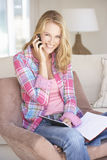 Young Woman Doing Paperwork And Using Mobile Phone At Home Stock Photography