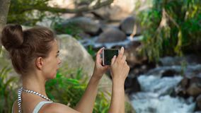 Young woman doing photo landscape on mobile phone while traveling in mountain waterfall in jungle forest. Woman tourist. Using smartphone for shooting video stock video