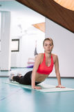 Young woman doing pilates exercises on the floor at the gym Stock Photos