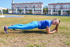 Young woman doing a plank exercise outside.  royalty free stock photography