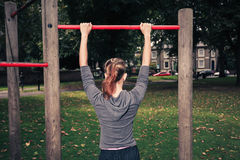 Young woman doing pullups in the park Stock Photo