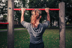 Young woman doing pullups in the park Royalty Free Stock Images