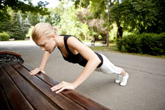 Young woman doing push ups. On bench in park Royalty Free Stock Image