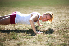 Young woman doing push ups exercise, workout on grass Stock Photos