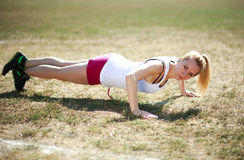 Young woman doing push ups exercise, workout on grass Royalty Free Stock Photo