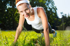 Young woman doing push ups on grass. Royalty Free Stock Photography