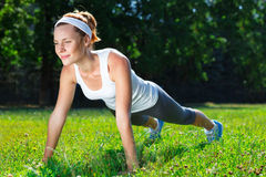 Young woman doing push ups on green royalty free stock photo