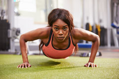 Young woman doing push ups at a gym Royalty Free Stock Images