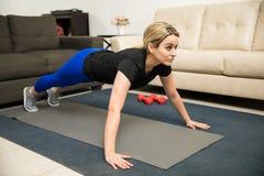 Young woman doing push ups at home. Good looking young Latin woman doing push ups at home on an exercise mat royalty free stock photography