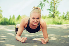 Young woman doing push ups outdoors in a park on sunny summer da Stock Image