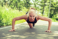 Young woman doing push ups outdoors in a park on sunny summer da Stock Photos