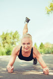 Young woman doing push ups outdoors in a park on sunny summer da Royalty Free Stock Images