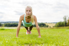 Young woman doing push-ups in the park Royalty Free Stock Image