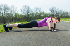 Young woman doing push ups . Royalty Free Stock Photos