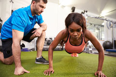 Young woman doing push ups under supervision of a trainer Royalty Free Stock Photo