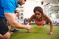 Young woman doing push ups under supervision of a trainer. Young women doing push ups under supervision of a trainer Royalty Free Stock Photography