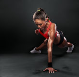 Young Woman Doing Push-Ups. Workout fitness posture body building exercise exercising on studio Stock Image