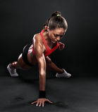 Young Woman Doing Push-Ups. Workout fitness posture body building exercise exercising on studio Royalty Free Stock Photography