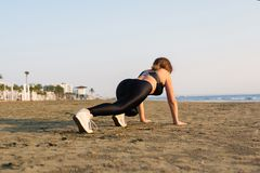 Young woman doing pushups on beach. royalty free stock photo