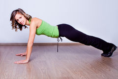 Young woman doing pushups on the floor Royalty Free Stock Photo