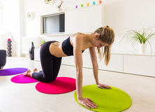 Young woman doing pushups in her living room Stock Photos
