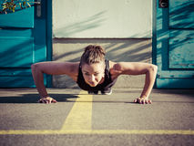 Young woman doing pushups outdoors Royalty Free Stock Image