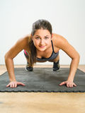 Young woman doing pushups Stock Images