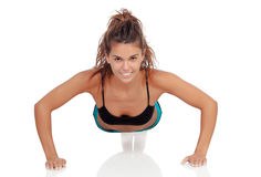 Young woman doing pushups. Young woman doing push-ups isolated on a white background royalty free stock images