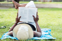Young woman doing reading at rest. This young woman lying in the shade of a tree is reading quietly Stock Images