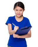 Young woman doing research with clipboard Stock Photo