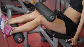 Young woman doing seated leg curls in sports club indoors. Attractive athlete prepares legs and buttocks stock video