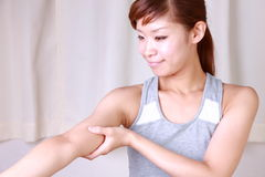 Young woman doing self arm massage Stock Images