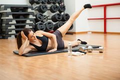 Young woman doing side crunches at the gym royalty free stock photos