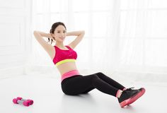 Women doing sit-ups on floor at home Stock Photography