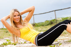 Young Woman Doing Sit-Ups on a Grassy Beach Royalty Free Stock Photography