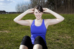 Young woman doing sit-ups outdoors Stock Photography
