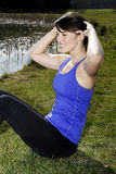 Young woman doing sit-ups outdoors Royalty Free Stock Images