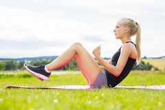 Young woman doing sit ups in the park Stock Photos