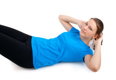 Young woman doing sit ups. Sporty girl doing sit ups on a white background Stock Photo