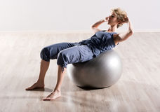 Young woman doing sit ups on stability ball Royalty Free Stock Images