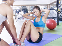 Young woman doing sit-ups. Young women doing sit-ups with help from her partner Royalty Free Stock Photo