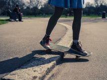 Young woman doing skateboard trick on curb Stock Photo