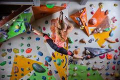 Young woman doing splits to reach next handhold while bouldering. Young woman bouldering on overhanging wall in indoor climbing gym, doing splits to reach next Royalty Free Stock Image