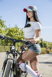 Young woman doing sports on the bike. Morning training Royalty Free Stock Photos
