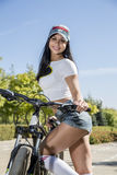 Young woman doing sports on the bike. Morning training Stock Photos