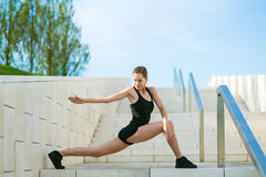 Young woman doing sports exercises in the park. Beautiful young woman doing sports exercises in the park Royalty Free Stock Photo