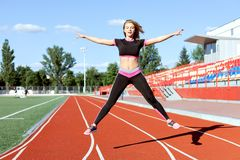 Young woman doing sports at the stadium. She makes jumps Royalty Free Stock Photo