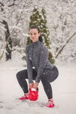 Young woman doing squat exercise with kettlebells in snow at win. Ter outdoor stock image