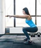 Young woman doing squats stock photos