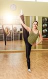Young woman doing standing split in fitness class Stock Images